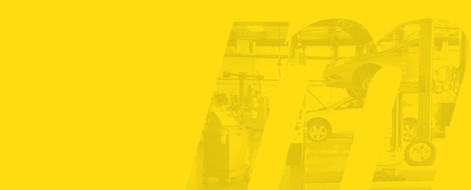 In the shape of an M and overlaid with yellow, two cards are being worked on in a Meineke car care center, one car is jacked up, the other car is ground level
