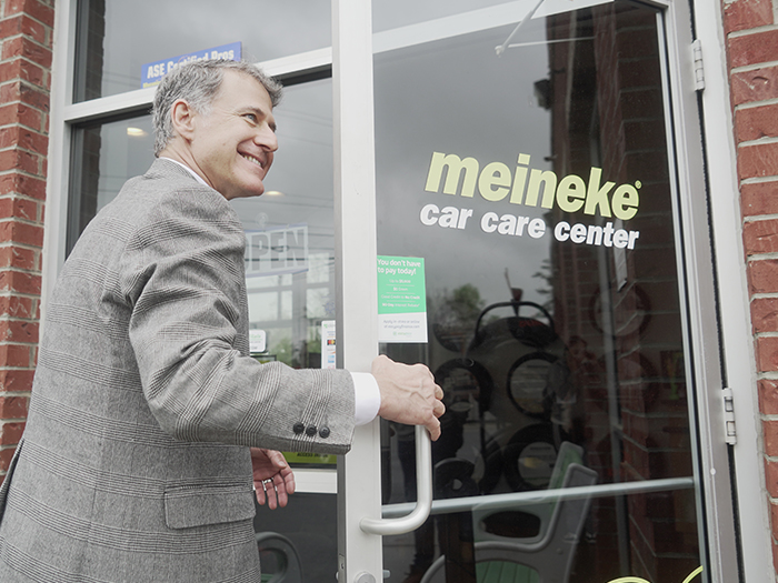 Smiling man entering Meineke car care center