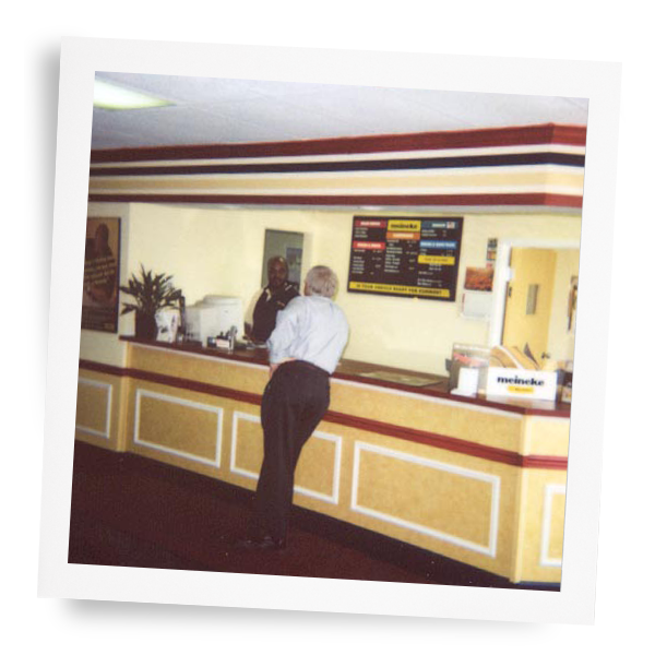 Older interior shot of customer waiting at front desk at a Meineke car care center