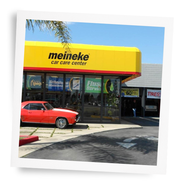 Exterior shot of Meineke car care center logo on building with a red car outside