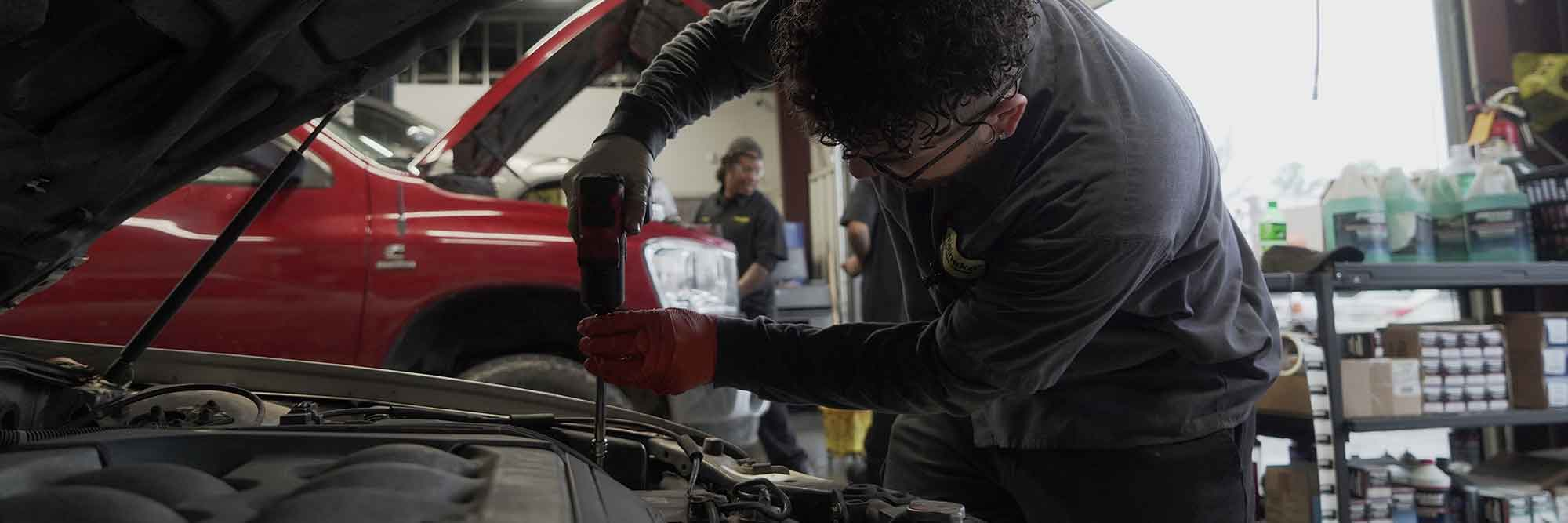 Meinke employee using a tool under the hood of a car in the Meineke center