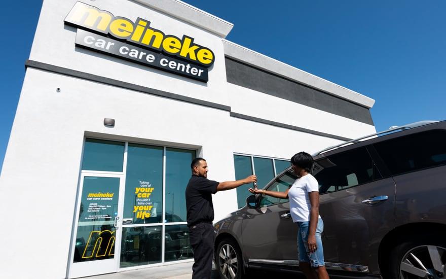 Meineke employee handing keys to customer