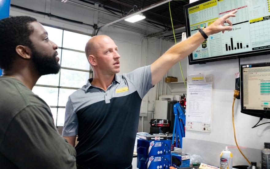 Meineke employee looking over data with customer